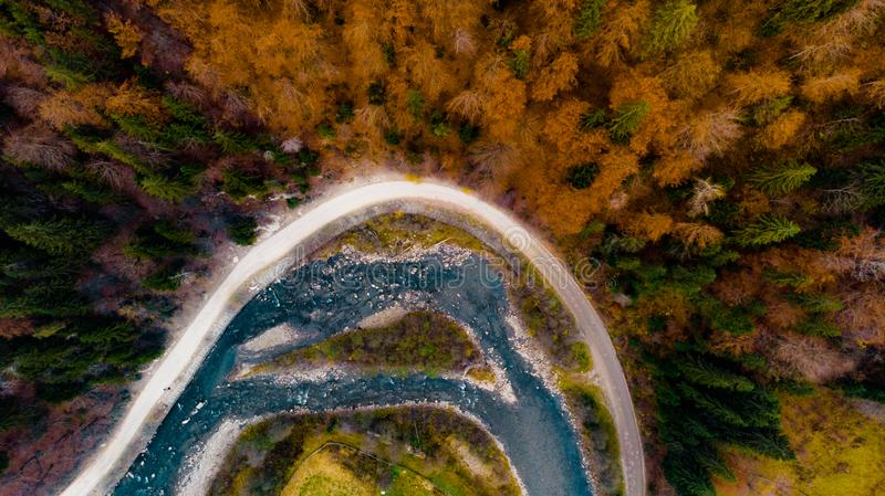 View from a drone to river, road and autumn forest in the Carpathian mountains stock photo