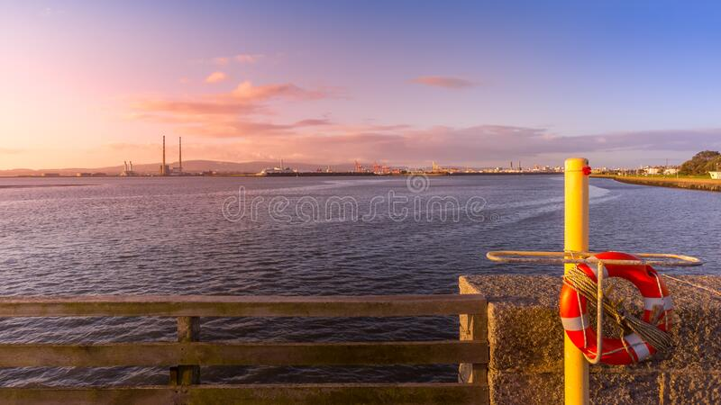 View on Dublin port with Poolbeg Power Plant, tall chimneys and dock cranes from Bull Island stock photos