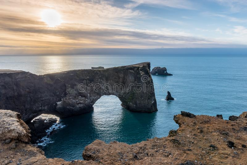 View of the Dyrholaey rock arch in Iceland at sunrise. View of the Dyrholaey cliffs and rock arch in Iceland at sunrise stock images