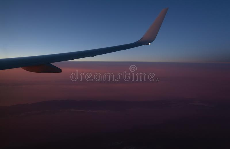 View of the earth from an airplane window from a height of 10,000 meters above the clouds illuminated royalty free stock image