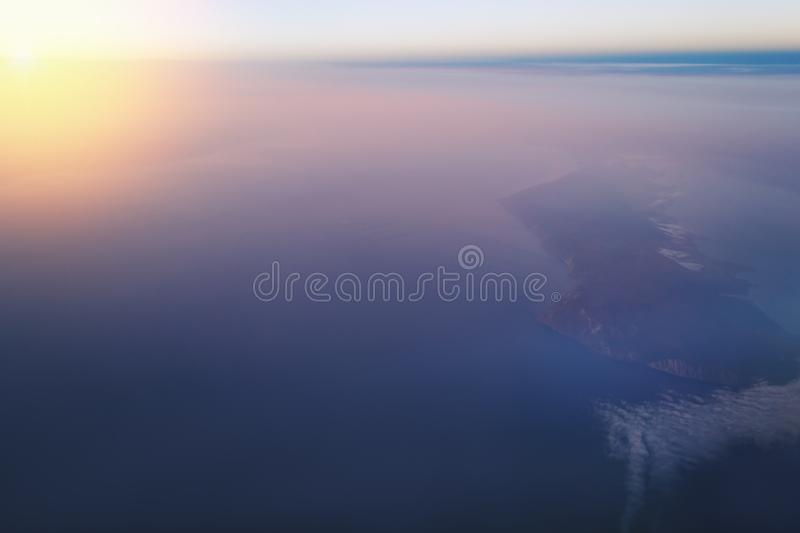View of the earth and Lake Baikal from the window of an airplane from a height of 10,000 meters. Above the clouds illuminated by the rays of the rising sun stock image