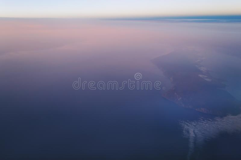 View of the earth and Lake Baikal from the window of an airplane from a height of 10,000 meters. Above the clouds illuminated by the rays of the rising sun stock images