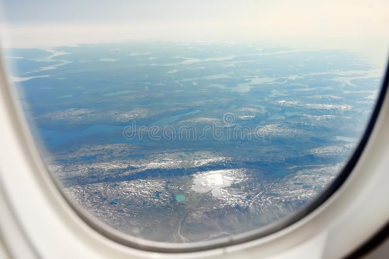 View earth from window of airplane. Visible mountains, lake, rivers and clouds above them. High angle view. Sunset stock photo