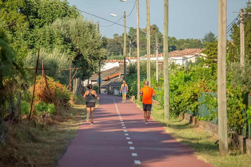 View of eco pedestrian / cycle lane, people running and walking with dog, trees village as background. Viseu / Portugal - 10 05 2018: View of eco pedestrian / stock image