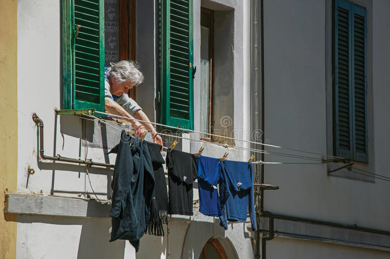 View of elderly woman putting clothes to dry at window in Colle di Val d`Elsa. royalty free stock photo