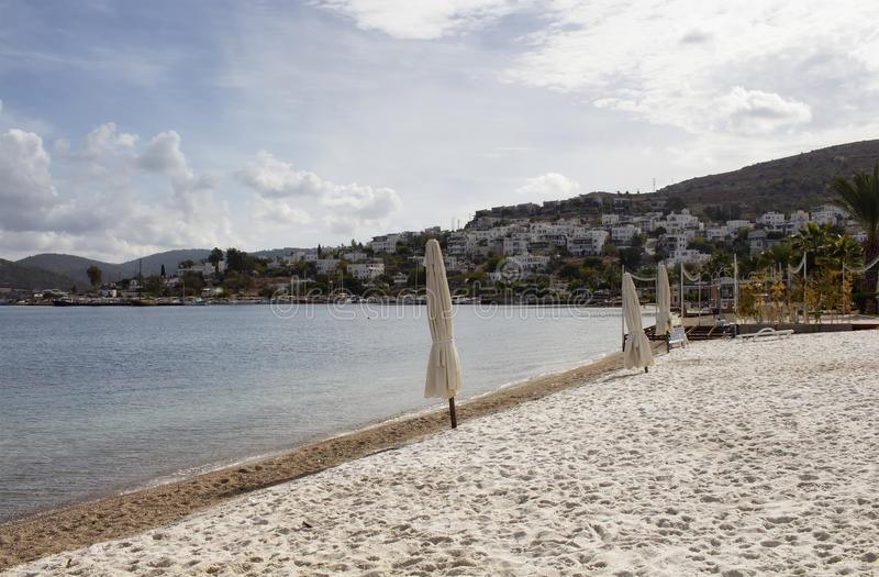 View of empty beach. Closed sun shades umbrellas, white summer houses and landscape in Turkbuku village on Bodrum peninsula in autumn. The image also shows how royalty free stock images