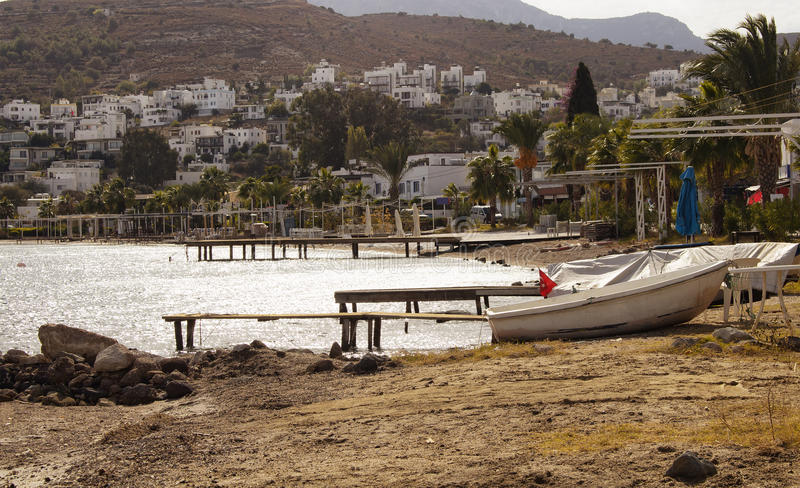 View of empty beach, small piers. And white small boat at Turkbuku village in Bodrum peninsula in autumn. The image also shows how tourism crises effects the royalty free stock images