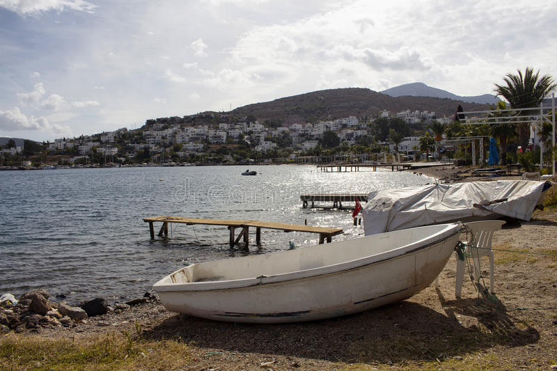 View of empty beach, small piers. And white small boat at Turkbuku village in Bodrum peninsula in autumn. The image also shows how tourism crises effects the royalty free stock photo