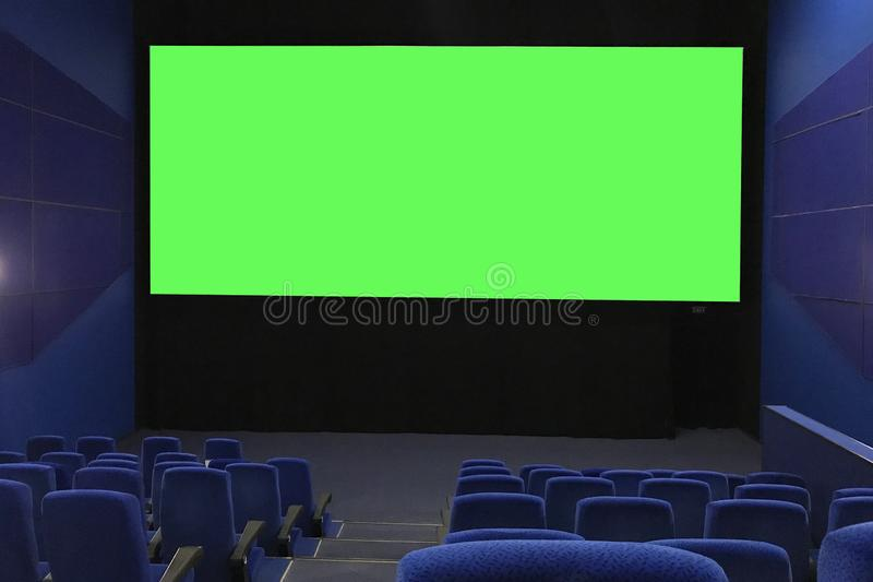 View of the empty cinema hall and a large green screen from the top rows. Cinema with rows of blue chairs royalty free stock photography