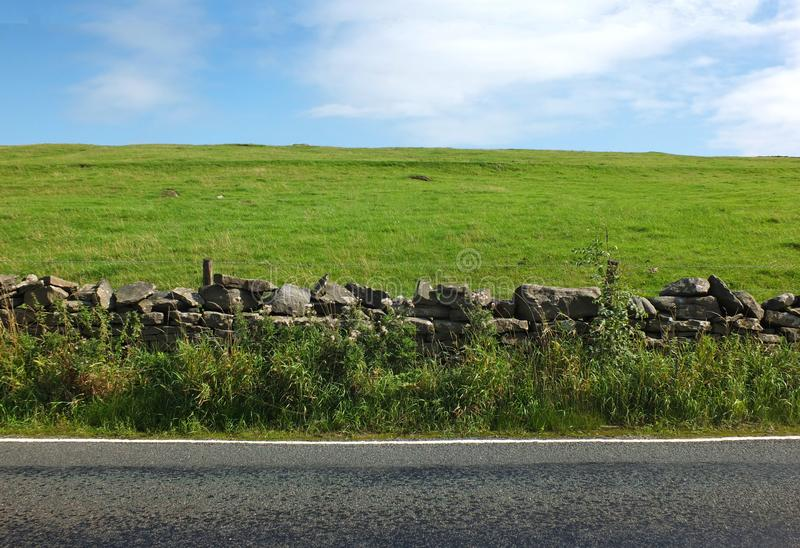 View of an empty country road with an overgrown dry stone wall with a fence separating it from a bright green hilly meadow. With blue summer sky and white royalty free stock photo