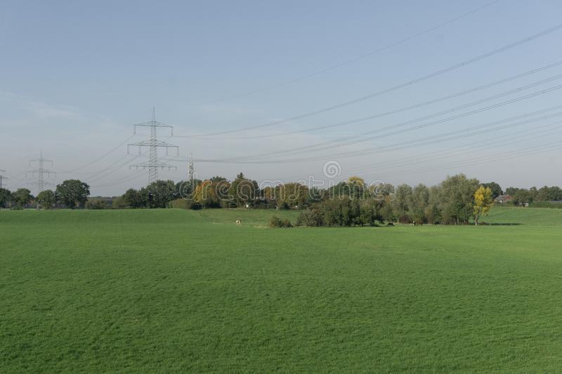 View of an empty green field with a lonely tower power line royalty free stock photos