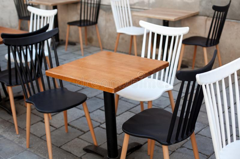 View of empty outdoor terrace cafe outdoor with retro wooden chairs and table in sunny summer day stock images