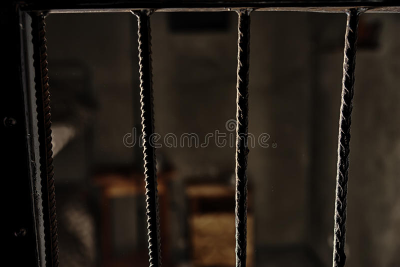 View of the empty prison cell through the bars royalty free stock image