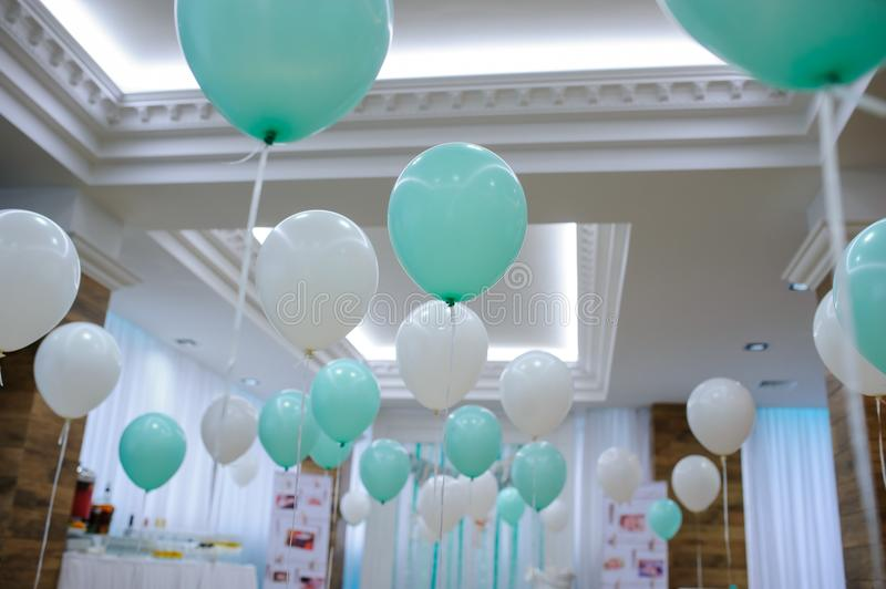 Restaurant decorated with white and turquoise balloons. View of an empty studio restaurant decorated with white and turquoise balloons on baptism party royalty free stock photography