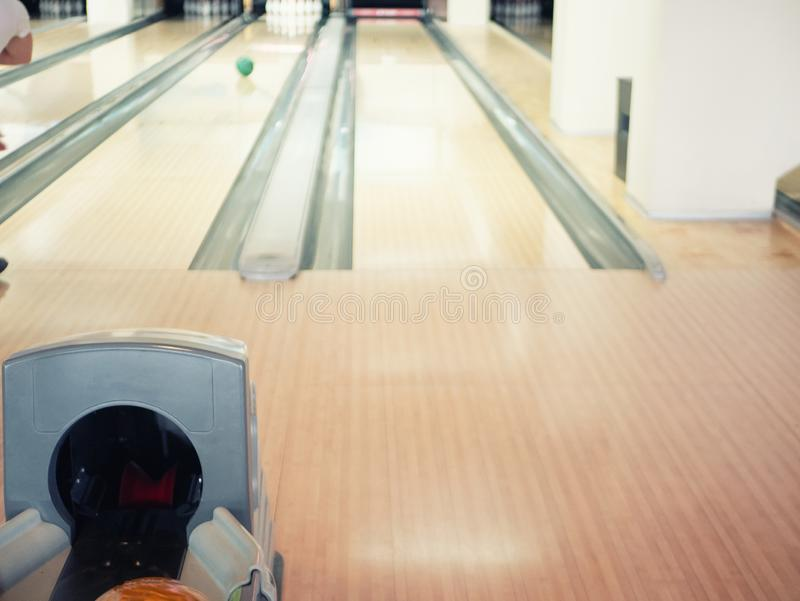 View on empty track at bowling club. blurred background with man throwing ball at pins.  stock photography