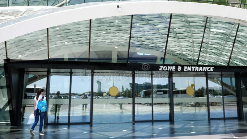 View at the entrance of airport with woman entering the door. stock photo