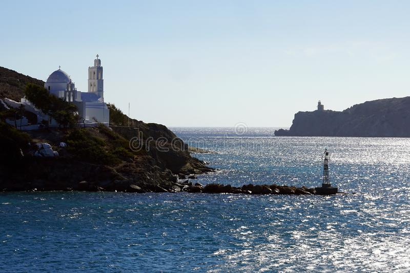 View of the entrance to the port of Ios with its lighthouse and the church of Saint Irene. View of the entrance to the port of Ios with its typical lighthouse royalty free stock photo