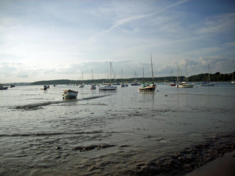River with boats. View of estuary over mud with boats moored in the distance. Background of blue sky with white clouds stock photography