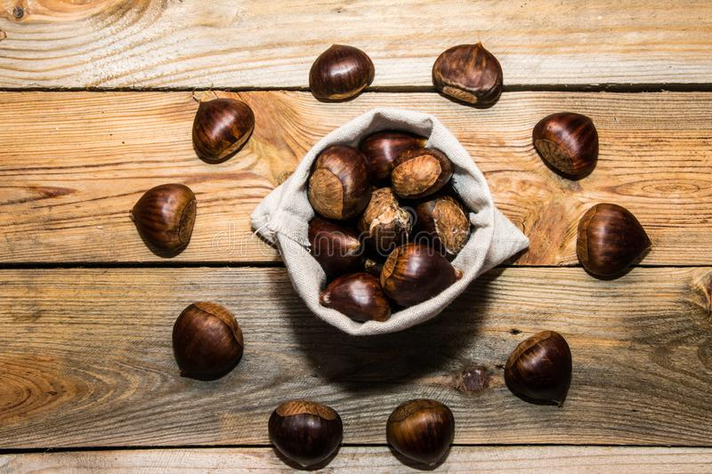 View of a fabric sack full of chestnuts surrounded by other chestnuts on a wooden background royalty free stock photo