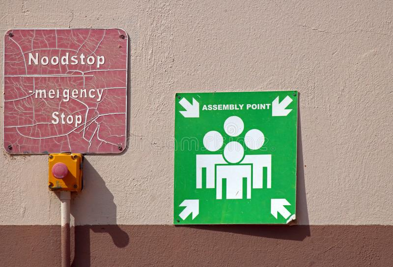 WEATHERED EMERGENCY SIGNS ON A WALL. View of faded signs against a wall indicating emergency measures to be taken when needed stock photography