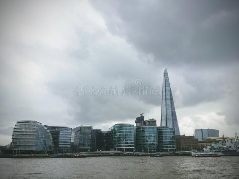 A view of the famous London City Hall from the bank of river Thames against a dramatic cloudy sky. London, UK stock photography