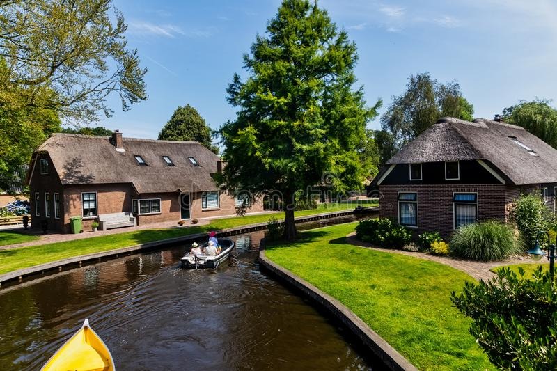 View of famous village Giethoorn with canals in the Netherland. Giethoorn, Netherlands - July 4, 2018: view of famous village Giethoorn with canals in the royalty free stock photo