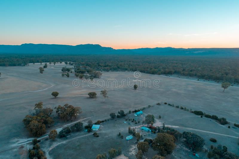 View of farmland and native forest with mountains. Aerial view of farmland and native forest with mountains in the background at dusk. Grampians, Victoria stock image