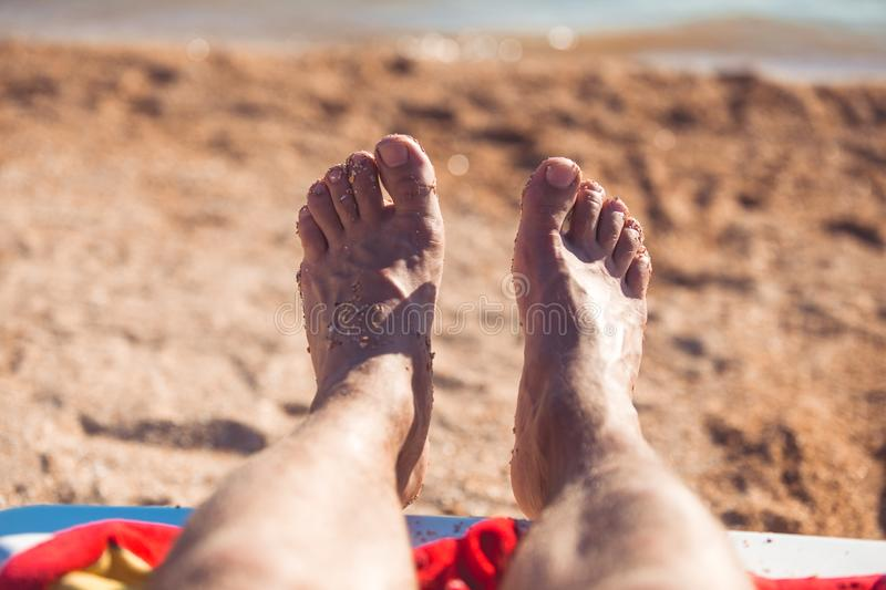 View of feet of man which are covered with sand on a beach stock images