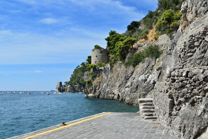 Positano jetty and towers. View from the ferry port of Positano along the coast with some towers on the hillside, Italy stock image