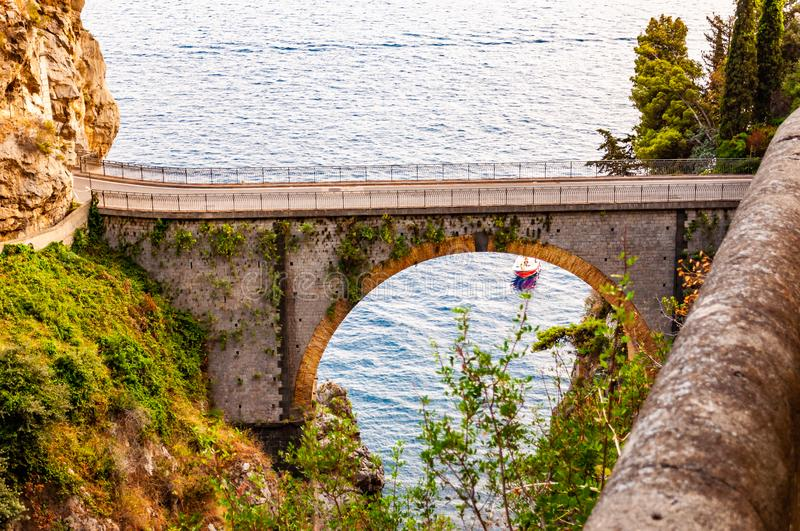 View on Fiordo di Furore arc bridge built between high rocky cliffs above the Tyrrhenian sea bay in Campania region. Boat floating. View on Fiordo di Furore arc royalty free stock images