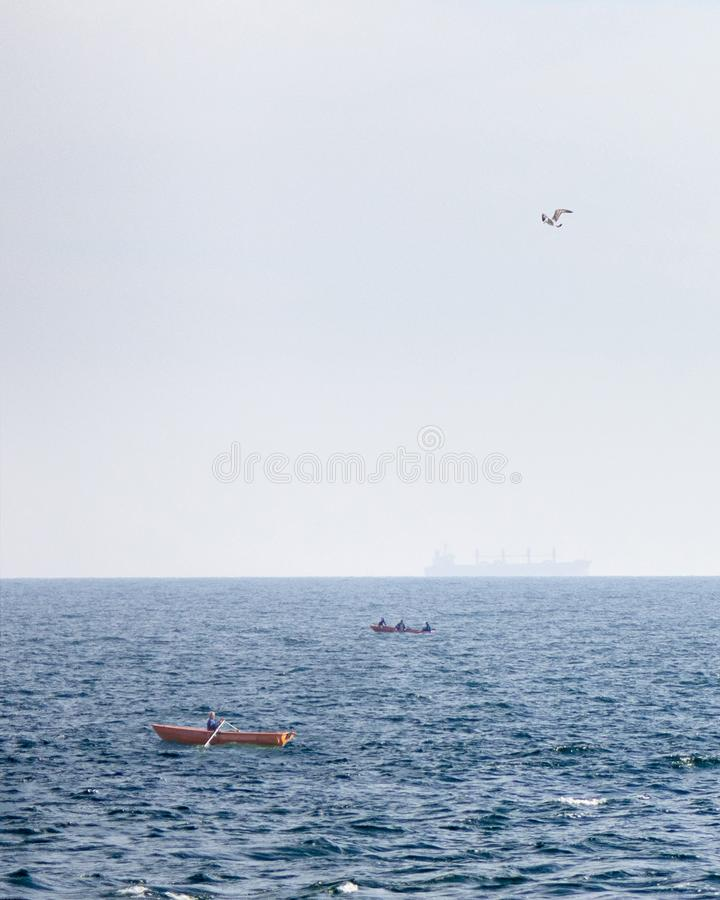 View of fishing boats on a background of blue open sea and a tanker blurred on the horizon stock images