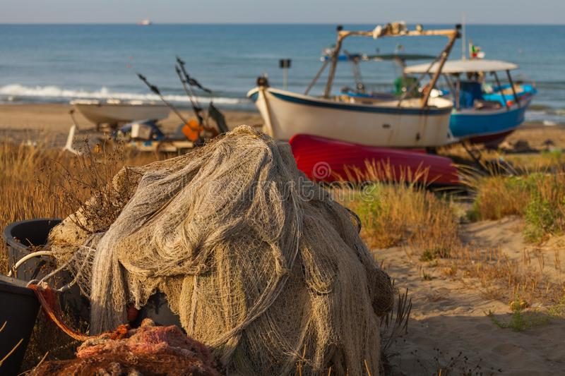 A view of a fishing net in front of the boat on the beach. Beautiful calm sea and water during an hot summer day royalty free stock photo