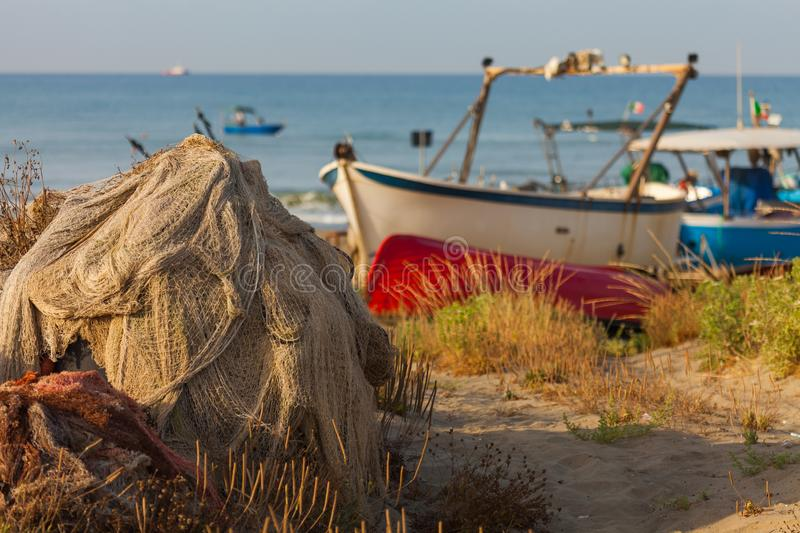 A view of a fishing net in front of the boat on the beach. Beautiful calm sea and water during an hot summer day stock photo
