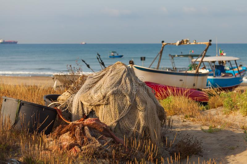 A view of a fishing net in front of the boat on the beach. Beautiful calm sea and water during an hot summer day royalty free stock photography