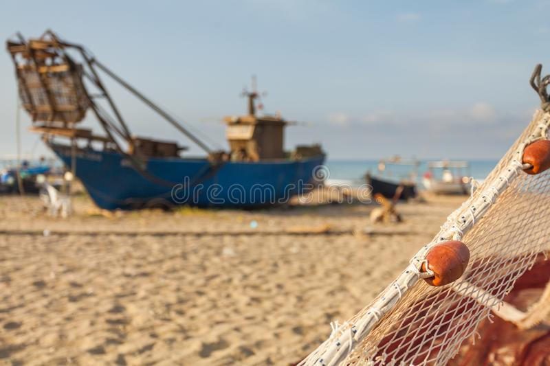 A view of a fishing net in front of the boat on the beach. Beautiful calm sea and water during an hot summer day stock photography