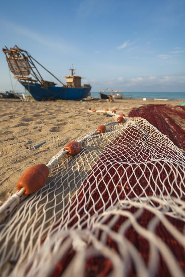 A view of a fishing net in front of the boat on the beach. Beautiful calm sea and water during an hot summer day stock image