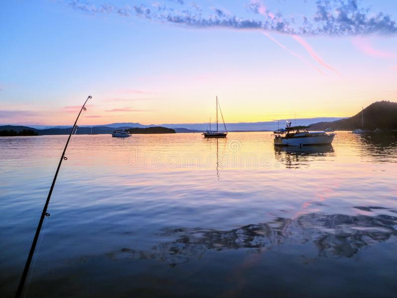 View of a fishing rod tip as someone fishes during sundown in a beautiful bay with a few boats anchored. stock images