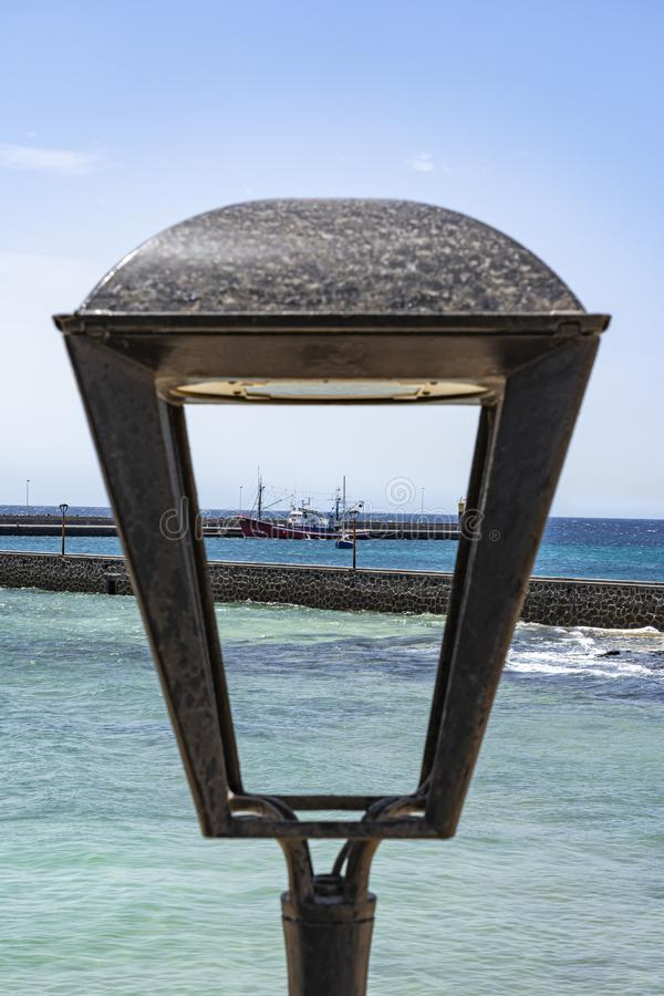View of a fishing vessel by a lantern at the old fortress Castillo de San Gabriel, Arrecife, Lanzarote, Spain royalty free stock images
