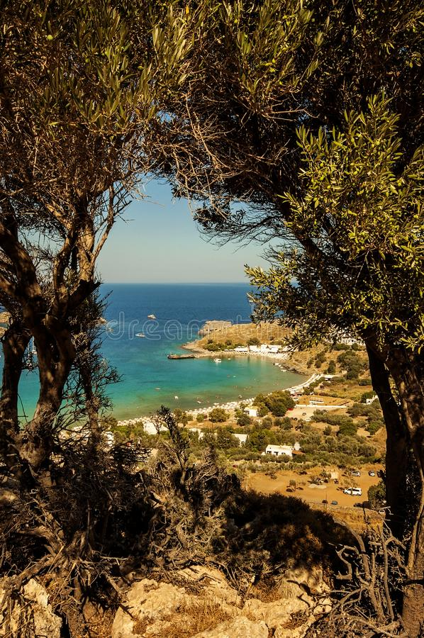 A view flanked with trees to a little village Lindos in Rhodes, Greece. A view flanked with trees to a little village Lindos in Rhodes Greece royalty free stock image