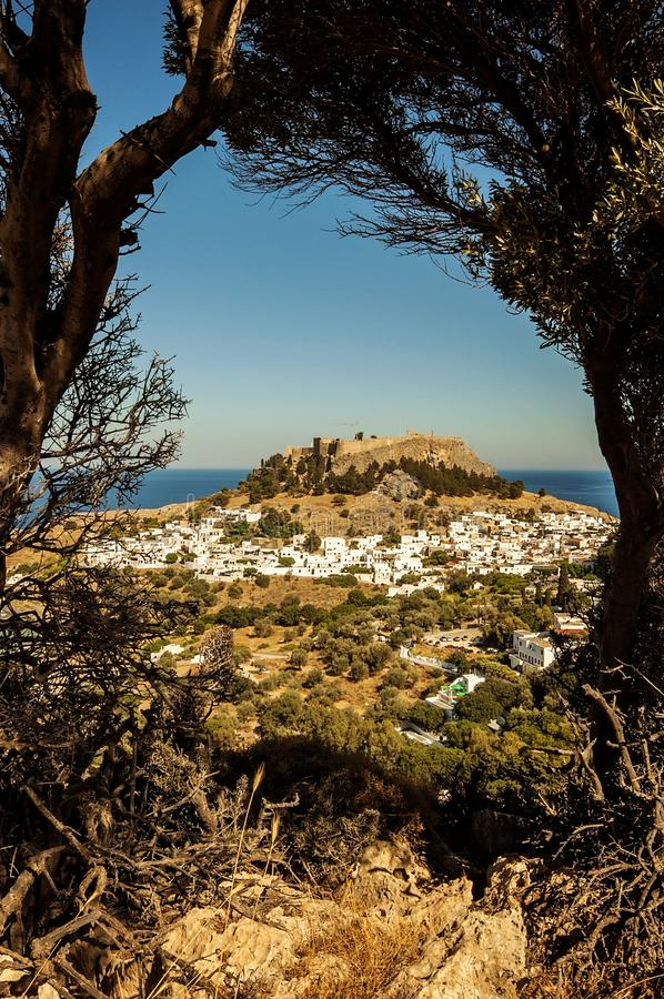 A view flanked with trees to a little village Lindos in Rhodes, Greece and an old castle in the middle. A view flanked with trees to a little village Lindos in royalty free stock photos