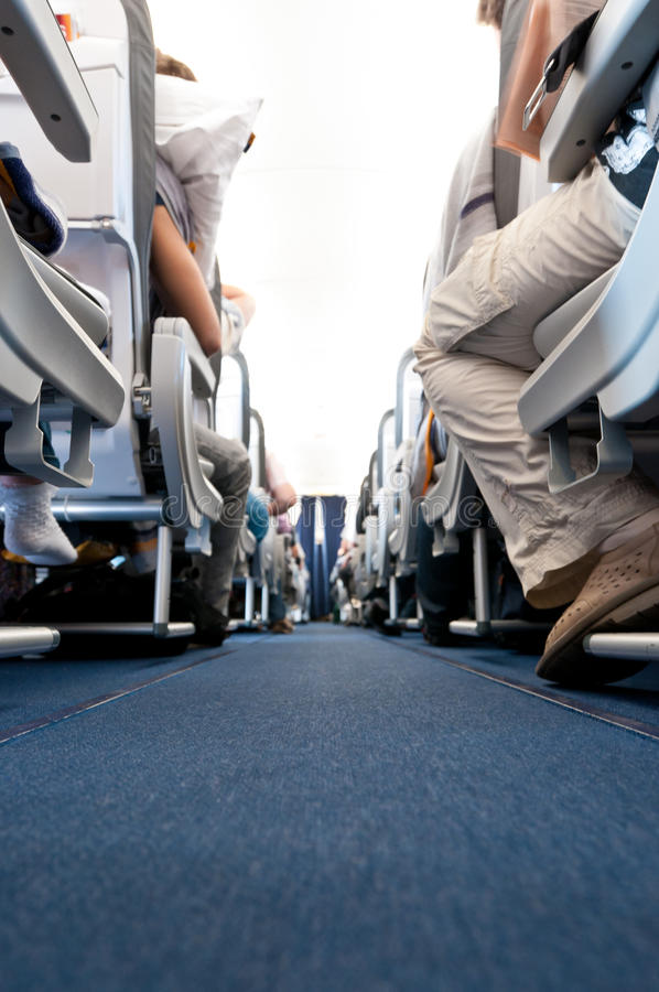 View from floor of plane cabin on aisle. Low angle view of air plane cabin aisle with rows of seats by the sides. People on seats, none recognizable royalty free stock images