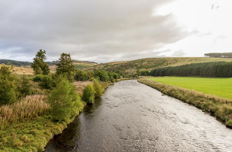 A view of the flowing river and low hills in cloudy weather, autumn in Cairngorms National Park. October 2017 stock image