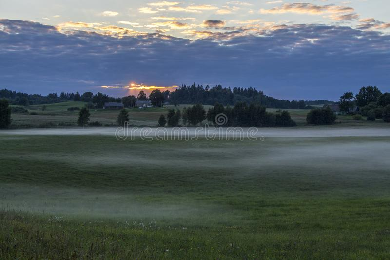 View of foggy green fields and meadows at sunset royalty free stock photography