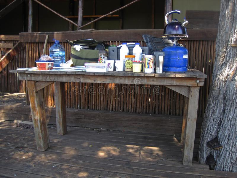 LUNCH PACKED OUT ON AN OLD TABLE AT AN ABANDONED HUNTER`S LODGE IN AFRICAN WILDERNESS royalty free stock images
