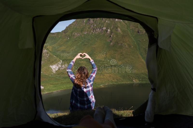 Personal perspective of a male camper in tent in the swiss alps with a young woman doing hand heart shape in front of him royalty free stock photography