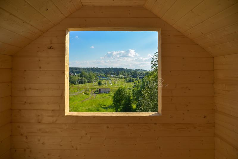 View of forest and village through window cut in wooden house. View of forest and village in summer through window cut in wooden house royalty free stock photos