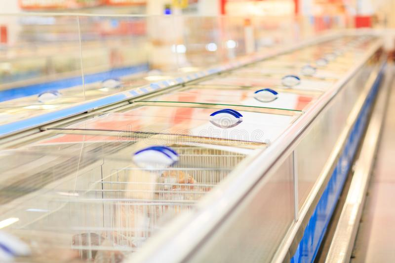 View of freezers in a super market on a blurred background. Freezers for food and frozen seafood are in the supermarket for customers. A lot of boxes for stock photo