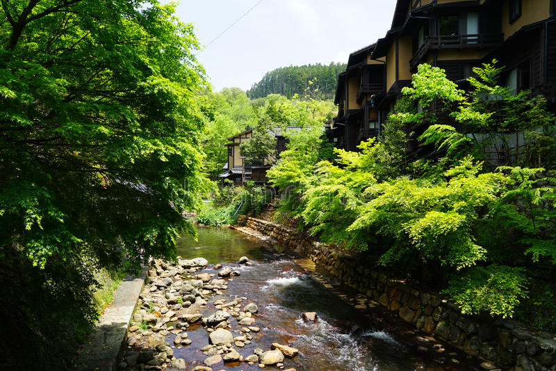 View of fresh stream with stone bank through green trees and local buildings on stone bank in Kurokawa onsen town royalty free stock photo