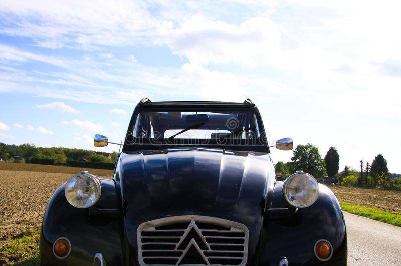 View on front of black French classic cult car 2CV with silver headlights and radiator grille in rural area stock images