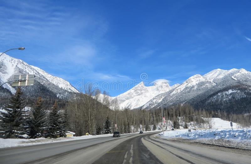The view through the front of a car driving down the highway through the Rocky Mountains on a sunny, beautiful day. Outside of Fernie, British Columbia, Canada royalty free stock photography